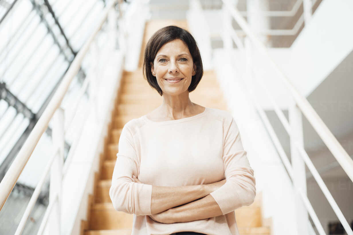 Smiling confident businesswoman with arms crossed against steps in corridor - JOSEF03840 - Joseffson/Westend61