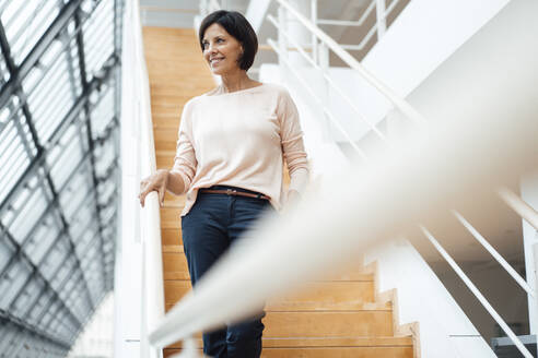 Businesswoman looking away while standing on steps in corridor - JOSEF03843