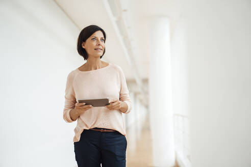 Mature female professional with digital tablet looking away while standing on corridor - JOSEF03846