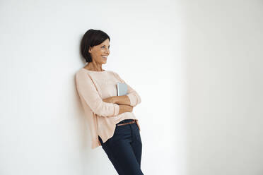 Smiling businesswoman with arms crossed against wall in office - JOSEF03849