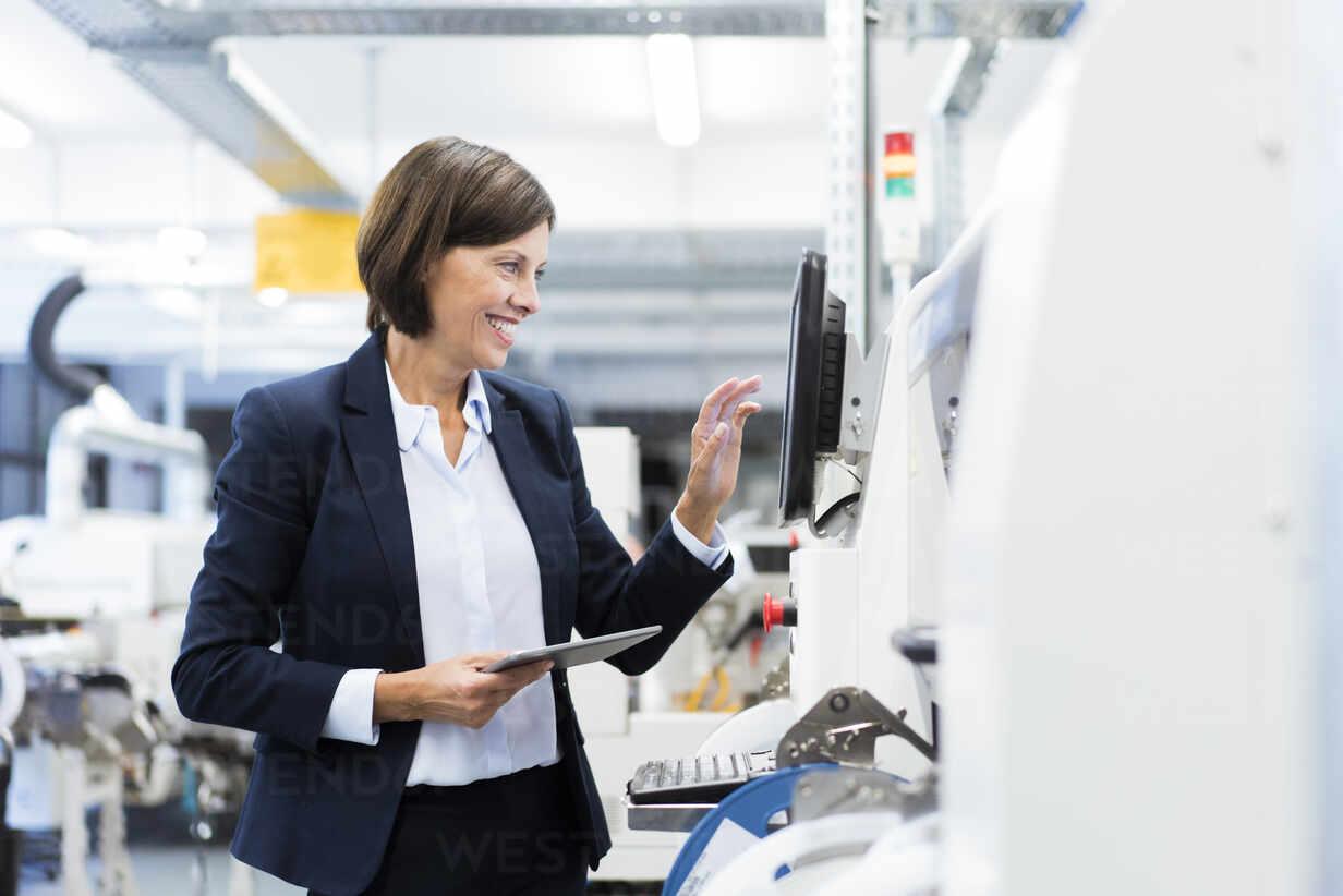 Glückliche Geschäftsfrau mit digitalem Tablet, die Maschinen in einer Fabrik bedient - JOSEF03855 - Joseffson/Westend61