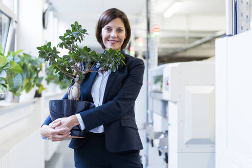 Smiling businesswoman holding potted plant in industry - JOSEF03858