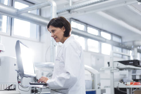 Female technician working on computer at factory - JOSEF03879