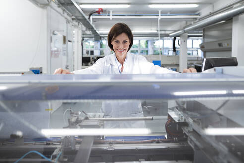 Smiling female technician by machinery in industry - JOSEF03882