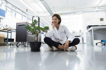 Female engineer with hand on chin sitting over floor in industry - JOSEF03885