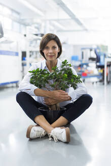Mature female entrepreneur embracing potted plant sitting in laboratory - JOSEF03888