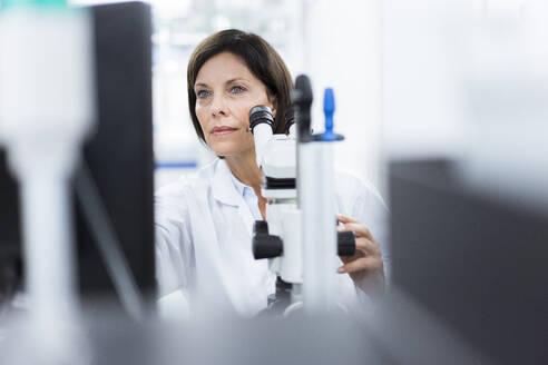 Female scientist with microscope at laboratory - JOSEF03894
