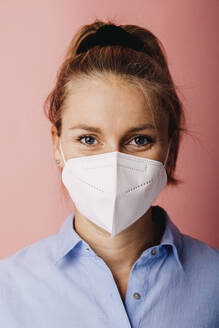 Mid adult businesswoman wearing protective face mask standing against colored background - DAWF01784