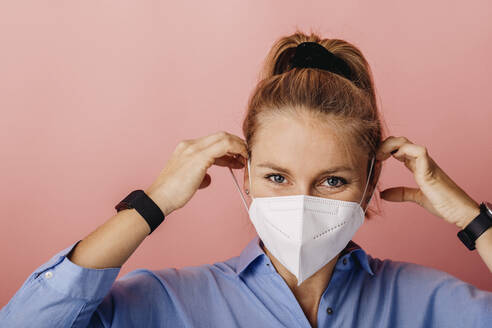 Businesswoman wearing protective FFP2 face mask while standing against colored background - DAWF01787