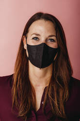 Young businesswoman wearing FFP2 face mask standing against colored background - DAWF01790
