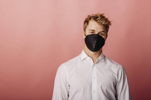 Young businessman wearing protective face mask staring while standing against colored background - DAWF01793