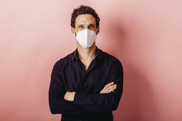 Mid adult businessman wearing FFP2 face mask standing with arms crossed against colored background - DAWF01796