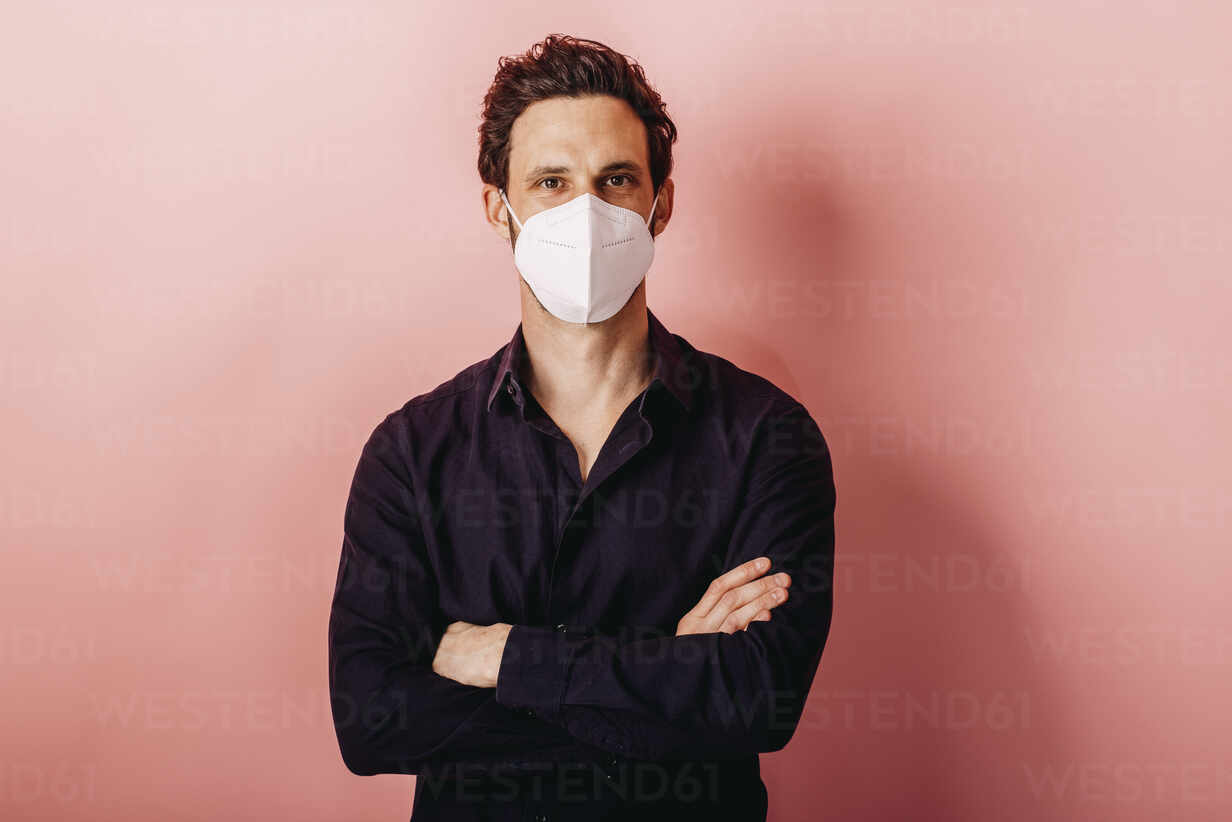 Mid adult businessman wearing FFP2 face mask standing with arms crossed against colored background - DAWF01796 - Daniel Waschnig Photography/Westend61