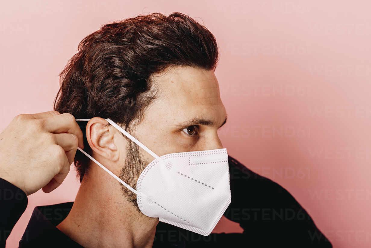 Mann mit FFP2 Maske vor Rosa Beige Hintergrund. Österreich, Kärnten, Klagenfurt - DAWF01799 - Daniel Waschnig Photography/Westend61