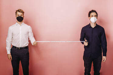 Business people measuring social distance with measuring tape while standing against colored background - DAWF01808