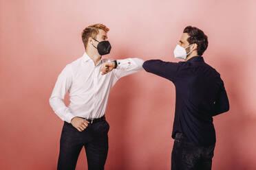 Zwei Personen mit Maske machen Corona Handshake vor farbigen Hintergrund. Österreich, Kärnten, Klagenfurt - DAWF01811