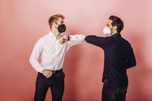 Entrepreneurs giving elbow bumps while greeting against colored background - DAWF01811