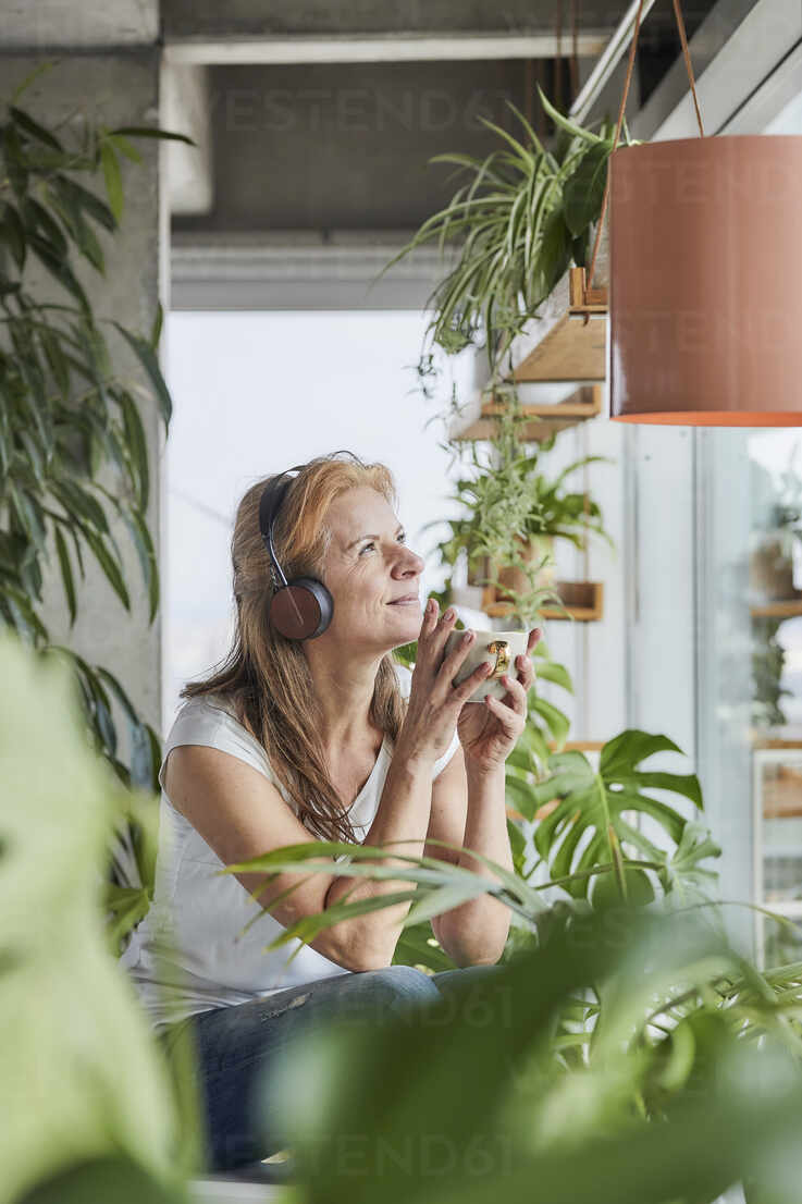Smiling woman with headphones holding coffee cup while looking away in loft apartment at home - FMKF06976 - Jo Kirchherr/Westend61