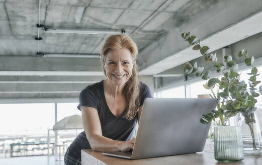 Smiling mature woman using laptop at table in balcony at home - FMKF06985