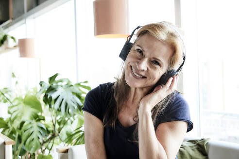 Beautiful smiling mature woman listening music through headphones at home - FMKF06991