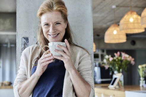 Smiling mature woman holding coffee cup against column at home - FMKF06994