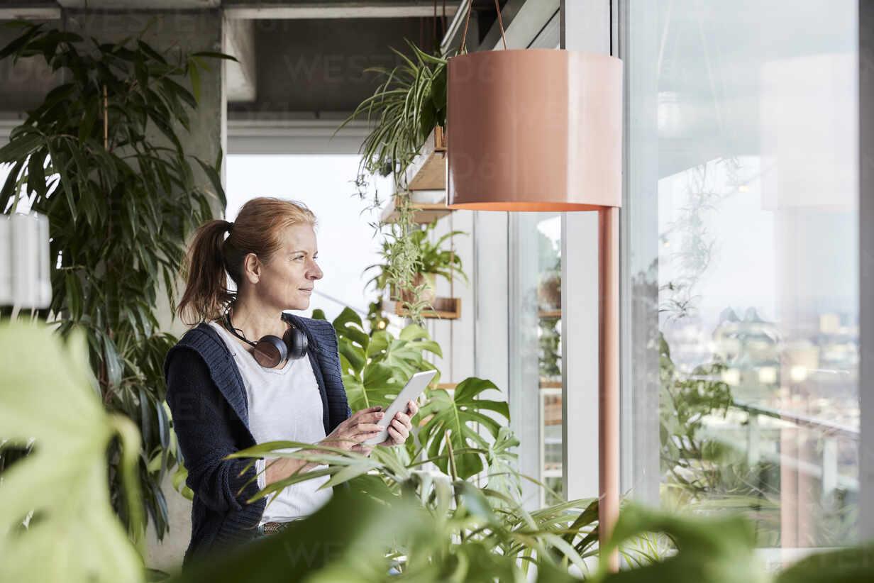 Frau mit Kopfhörern schaut durch das Fenster, während sie ein digitales Tablet auf dem Balkon zu Hause hält - FMKF07000 - Jo Kirchherr/Westend61