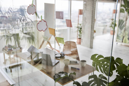 Adhesive notes on glass wall at office - FMKF07015