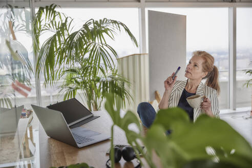 Businesswoman holding coffee cup while doing business plan at desk in home office - FMKF07021