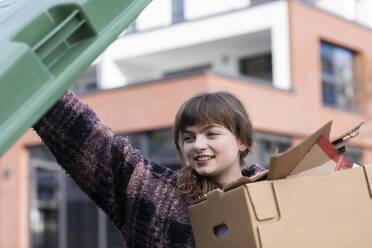 Young woman putting cardboard box in garbage bin - SGF02762