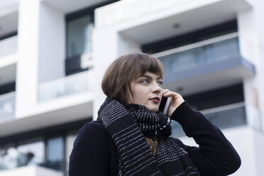 Young woman wearing scarf talking on mobile phone while standing against building - SGF02765