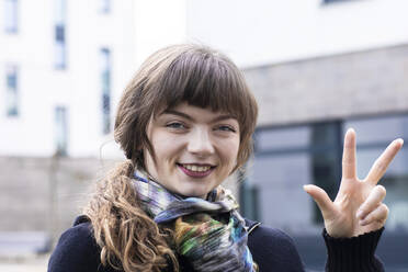 Junge Frau aussen macht Handzeichen mit Stadthäuser, Freiburg, BW, Germany - SGF02771