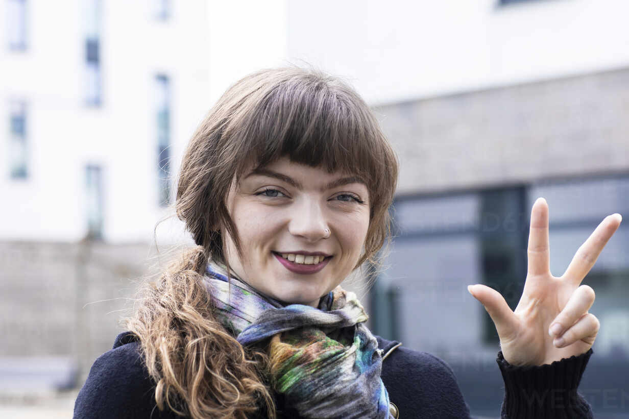 Smiling woman gesturing hand sign while standing outdoors - SGF02771 - Sigrid Gombert/Westend61