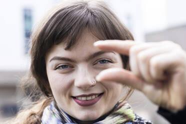 Junge Frau aussen macht Handzeichen mit Stadthäuser, Freiburg, BW, Germany - SGF02774