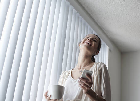 Smiling woman with coffee cup using mobile phone while standing by window at home - AJOF01095