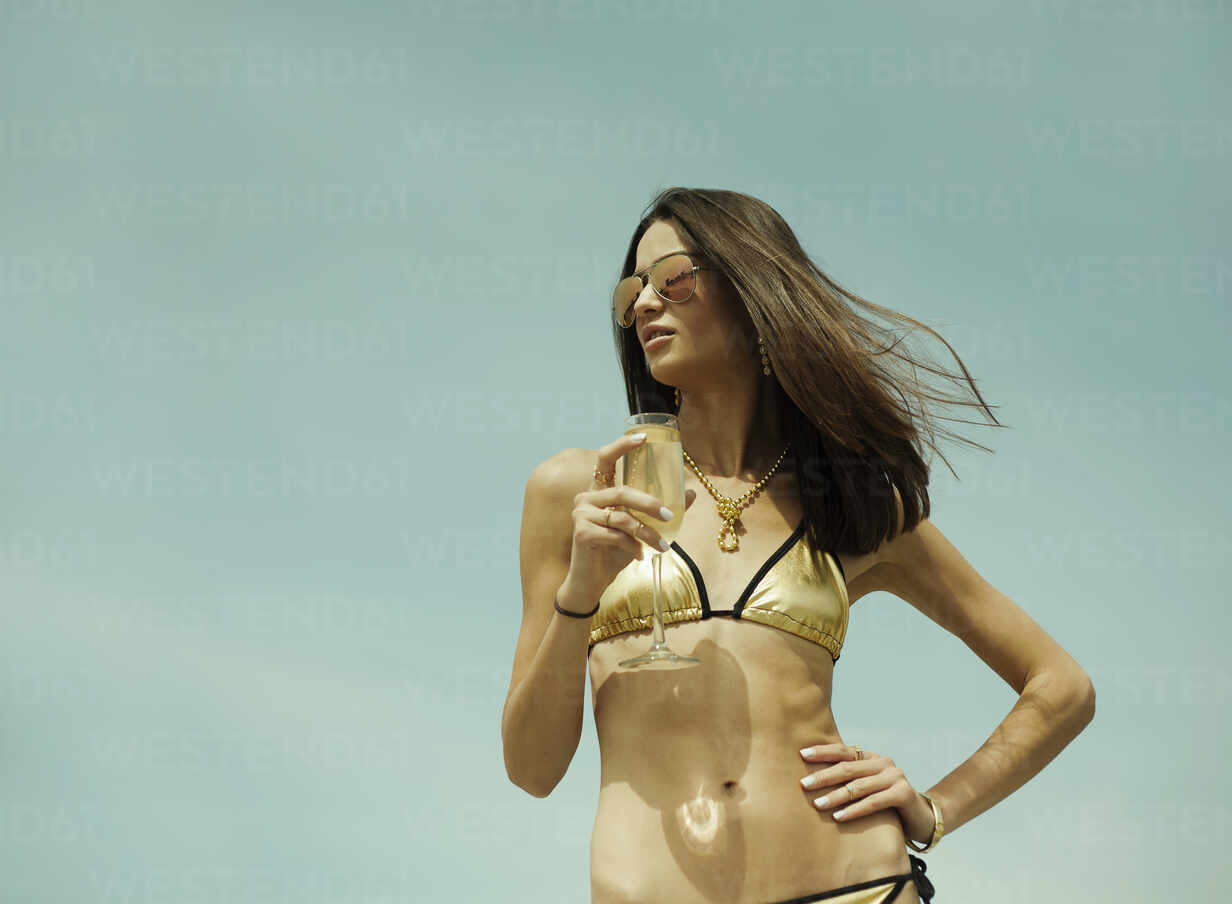 Woman wearing bikini and sunglasses drinking champagne while standing against sky - AJOF01101 - LOUIS CHRISTIAN/Westend61
