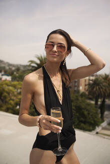 Smiling woman in one piece swimsuit holding champagne flute while standing against sky - AJOF01104