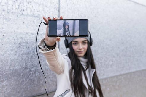 Teenage girl taking selfie through smart phone while listening music - JRVF00310
