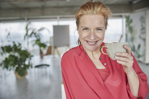 Beautiful mature woman with coffee cup at home - FMKF07044