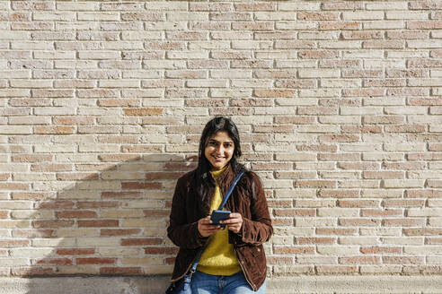 Smiling woman with sling bag holding mobile phone against brick wall - XLGF01220