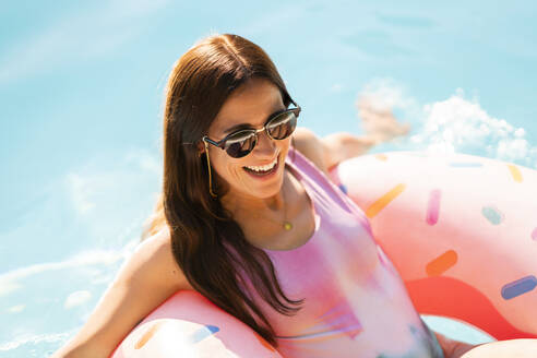 Smiling woman with inflatable ring floating on water during sunny day - AKLF00077