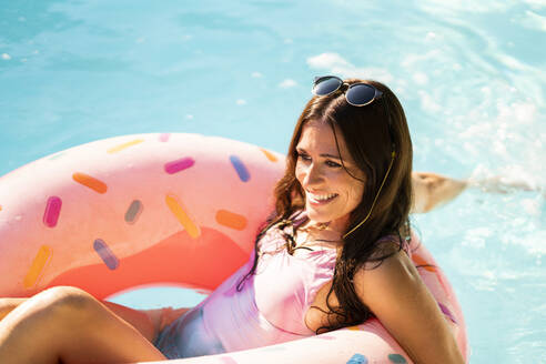 Smiling beautiful woman with inflatable ring floating on water while looking away during sunny day - AKLF00080
