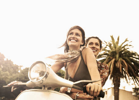 Smiling woman enjoying scooter ride with friend outdoors - AJOF01130