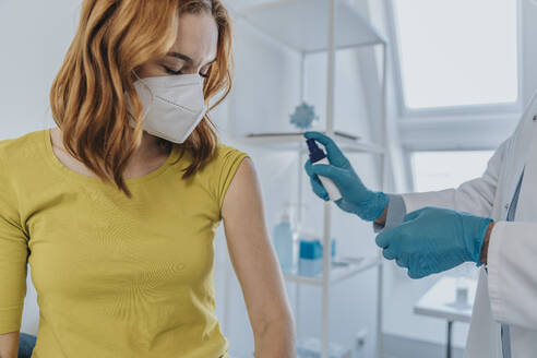 Doctor spraying on patient hand while preparing for vaccination at examination room - MFF07397