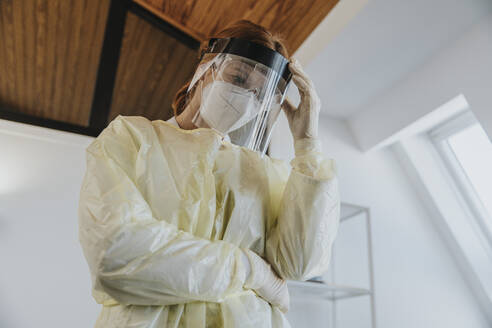 Female doctor wearing protective workwear standing with hand in hand at examination room - MFF07406