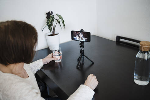 Woman holding glass of water while talking with daughter on mobile phone through video call - EBBF02583