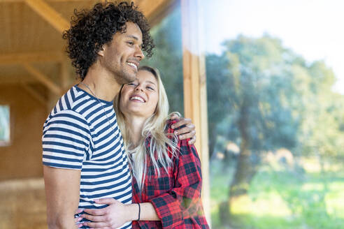 Smiling woman embracing man while standing at spacious room - SBOF02785
