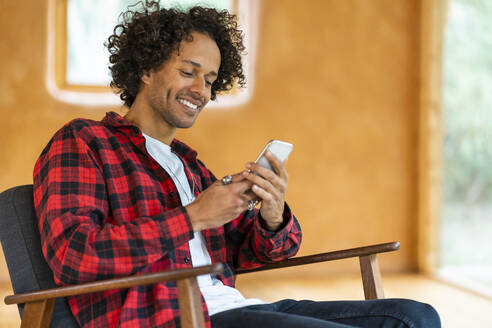 Young man using smart phone while sitting on armchair at spacious room - SBOF02812