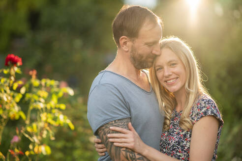 Deutschland, Hessen, Münzenberg, Paar umarmt sich im eigenen Garten, Eigenheim, Selbstverwirklichung, Beziehung, Liebe, Mann und Frau - AKLF00096