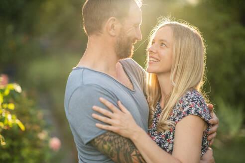 Deutschland, Hessen, Münzenberg, Paar umarmt sich im eigenen Garten, Eigenheim, Selbstverwirklichung, Beziehung, Liebe, Mann und Frau - AKLF00099