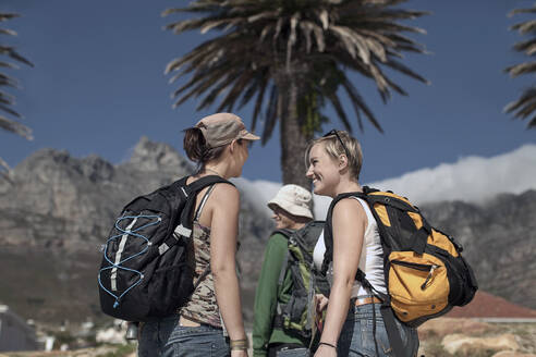 Two young women and man (22-26) wearing backpacks, Cape Town, South Africa - AJOF01156